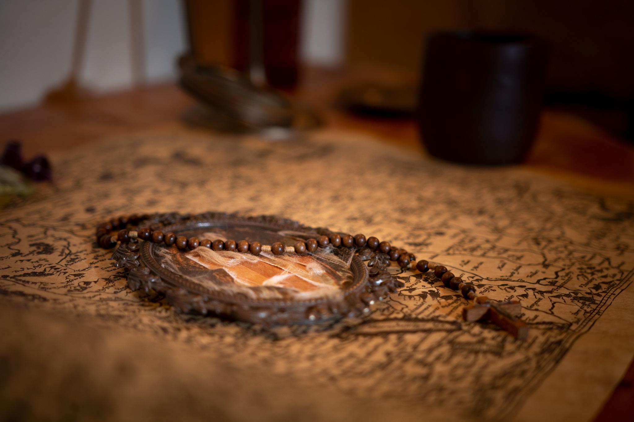 """Photographie d'une carte ancienne avec un médaillon et un chapelet prise dans la salle """"la colère de la vouivre"""" de fug game live escape Besançon. Photographie par le rat et l'ours graphiste."""