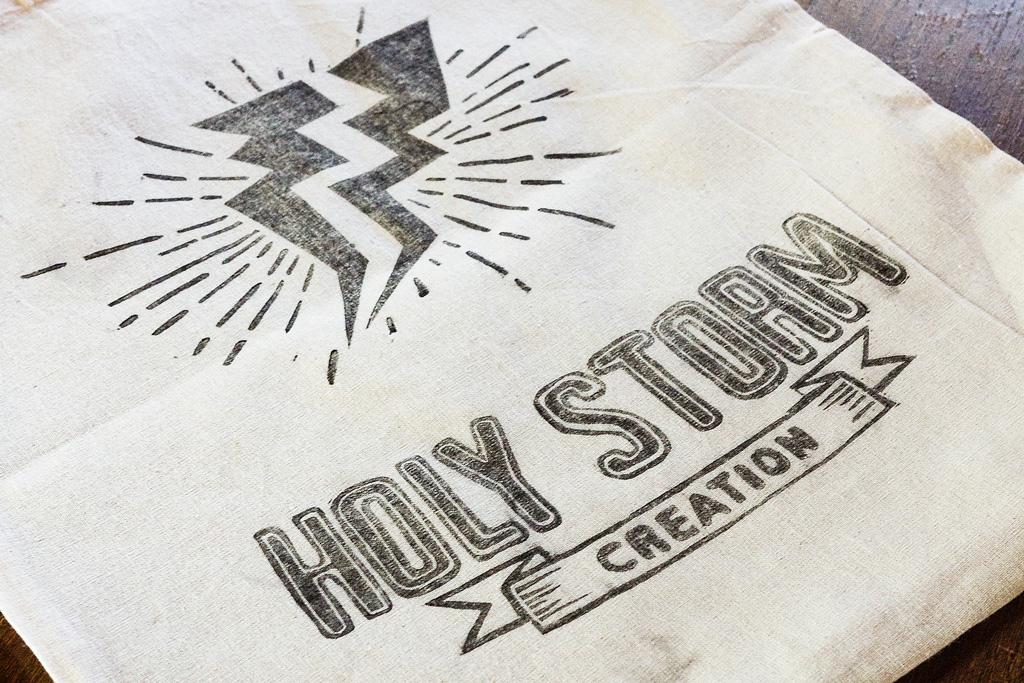 """Photo d'une linogravure sur sac en tissu pour l'activité de couture d'une créatrice Bisontine """"Holy storm Création"""" par le rat et l'ours graphiste."""